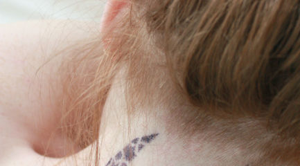 Tribal dotted sparrow tattoo on back of girl's neck