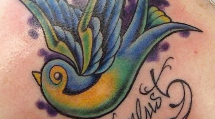 Wanderlust colorful swallow tattoo on back of girl's neck