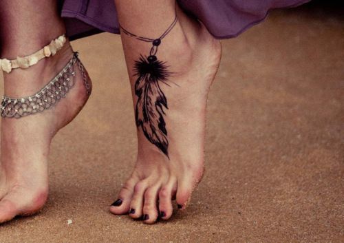 Black feather charm tattoo on girls ankle