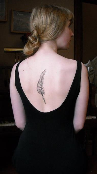 Black feather tattoo in middle of girls back