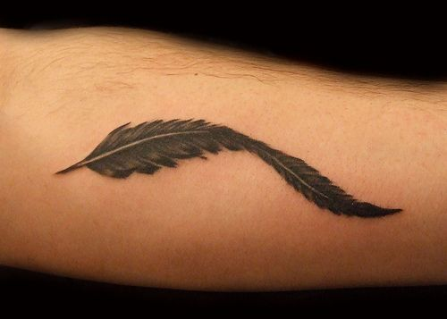 Black feather tattoo on guys arm