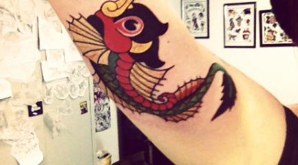 Colorful dragon fish tattoo on girls arm