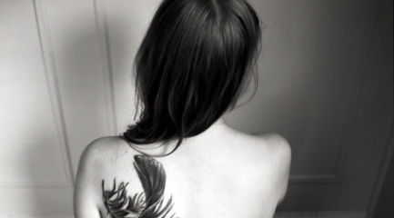 Large bird feather on back of girls shoulder