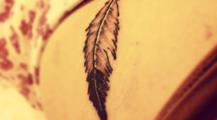 Simple back and white ruffled feather tattoo