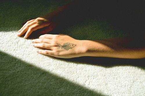 Small black and white fish hand tattoo