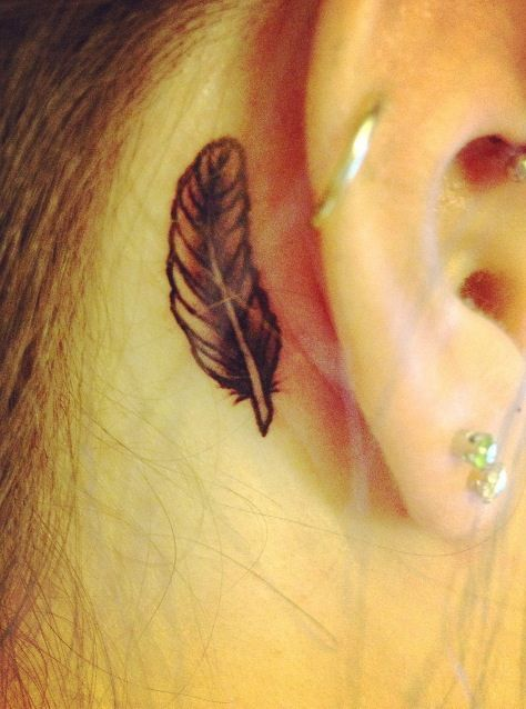 small black behind the ear feather tattoo