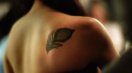 Small peacock feather on back of girls shoulder