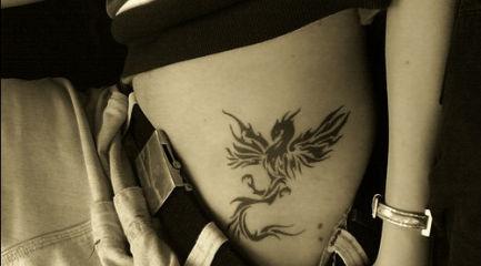 Black phoenix tattoo on girls waist