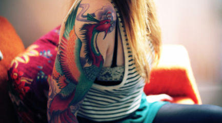Girls colorful phoenix tattoo on her arm