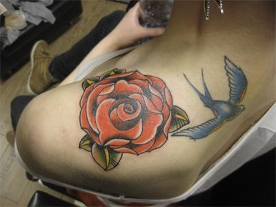 Blue swallow tattoo and rose on girls shoulder