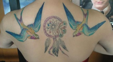 Colorful swallow tattoos around a dreamcatcher