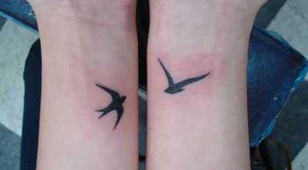 Small black swallow tattoos on wrists