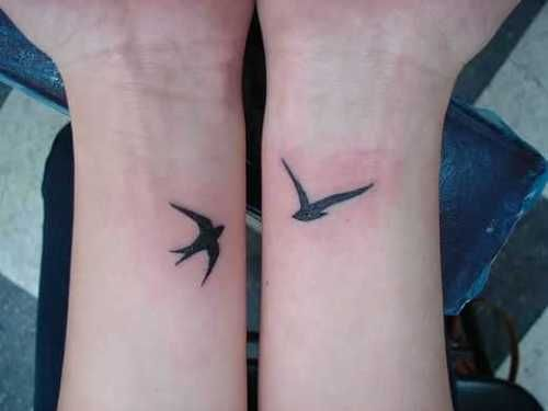 Small black swallow tattoos on wrists