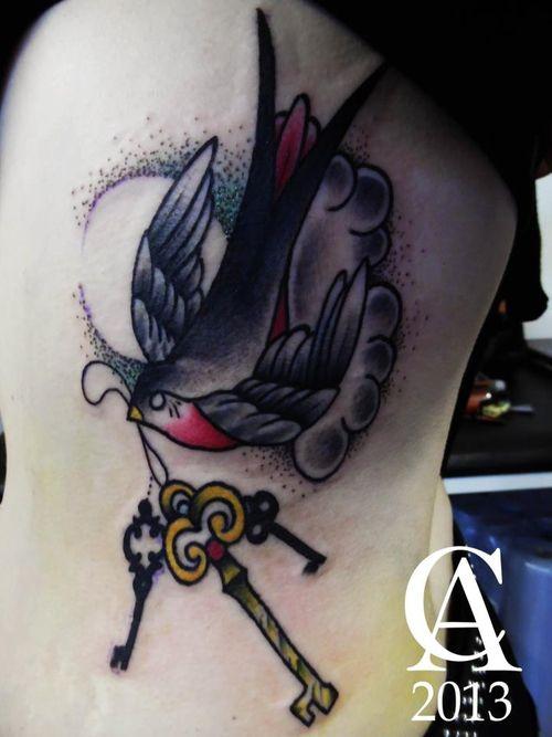 Swallow holding keys tattoo on girls side