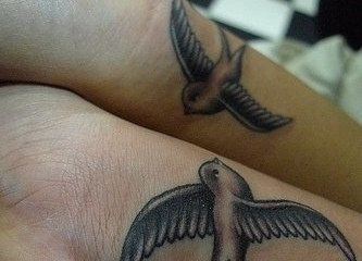 Two black swallow tattoos on bottom of wrists