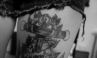 Big anchor tattoo on girl's thigh with flowers and banner
