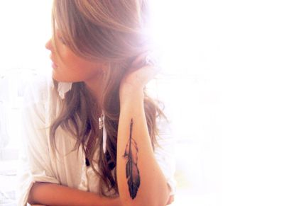 Black and white feather tattoo on girls arm