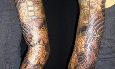 Full sleeve tattoo with hibiscus, Japanese patterns, and koi