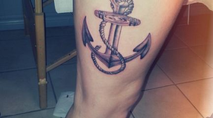 Large black traditional anchor tattoo on girl's thigh