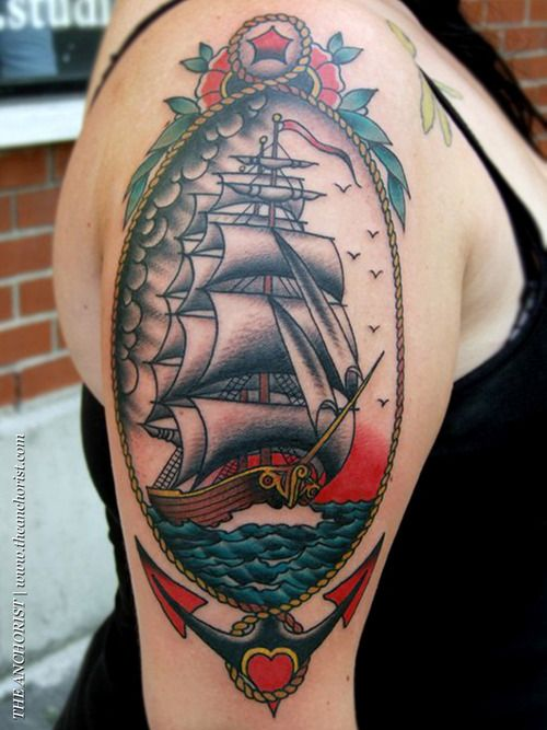 Large traditional anchor tattoo with nautical scene on arm