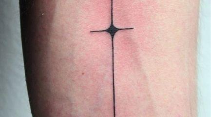 Long skinny black anchor tattoo on forearm