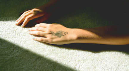Small black and white fish hand tattoo