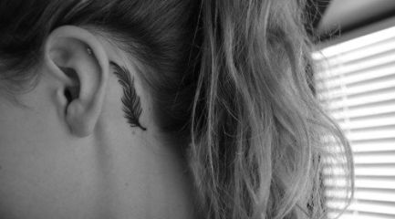 Small black feather tattoo behind girls ear