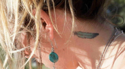 Small blue feather on girls neck behind her ear