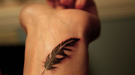 Small detailed black feather wrist tattoo