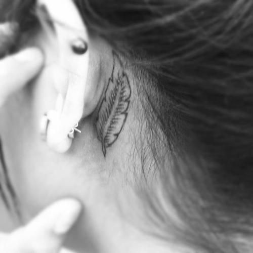 Small feather outline behind girls ear