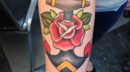 Traditional anchor and rose tattoo on forearm