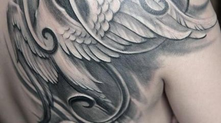 Black and white phoenix tattoo on back of girls shoulder