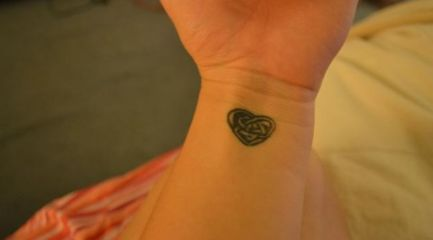 Cute Celtic knot and heart tattoo on girls wrist