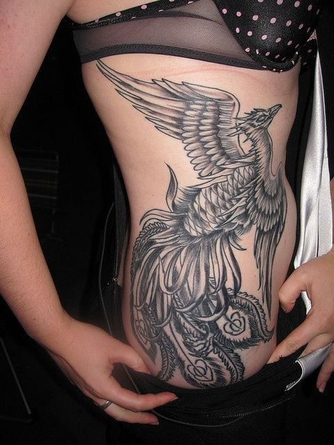 Phoenix rising tattoo on girls side in black