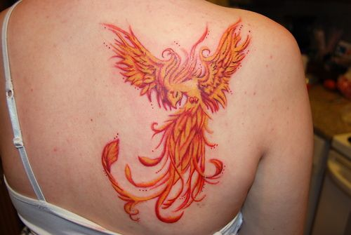 Phoenix tattoo on back of girls shoulder in fire colors