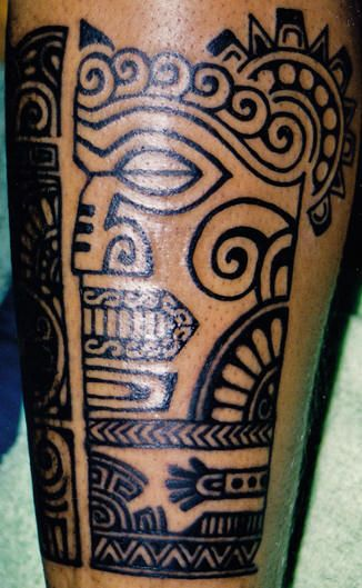 Polynesian totem face tattoo on guys leg