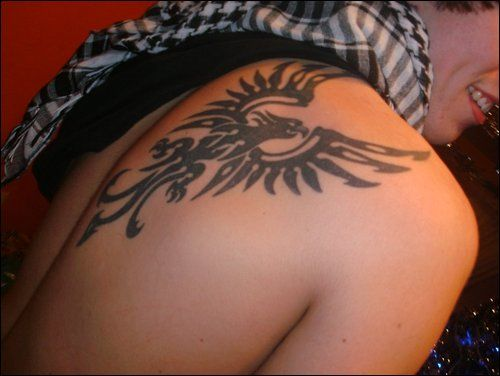 Tribal phoenix tattoo on guys shoulder